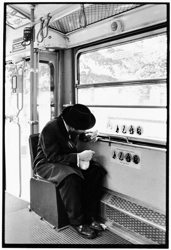 Rabbiner beim Studium einer Miniaturausgabe des Alten Testaments in einer Wiener Straßenbahn