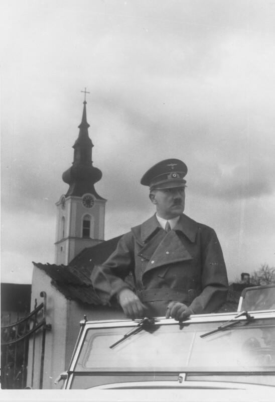 Adolf Hitler im offenen Auto vor der Pfarrkirche Leonding