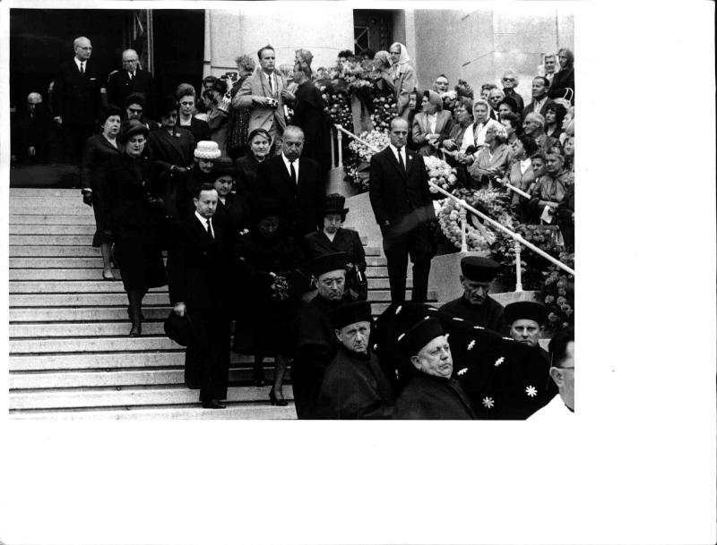 Begräbnis des Schauspielers Hans Moser am Wiener Zentral-friedhof, Leichenzug kommt aus der Kirche, der Sarg wird über eine Treppe getragen, dahinter der Zug der Trauergäste, an den Seiten zahlreiche Blumen-kränze und Begräbnisgäste