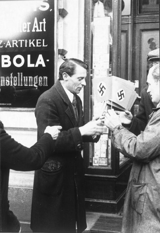 Mann verteilt Hakenkreuzfähnchen anlässlich des Einmarsches