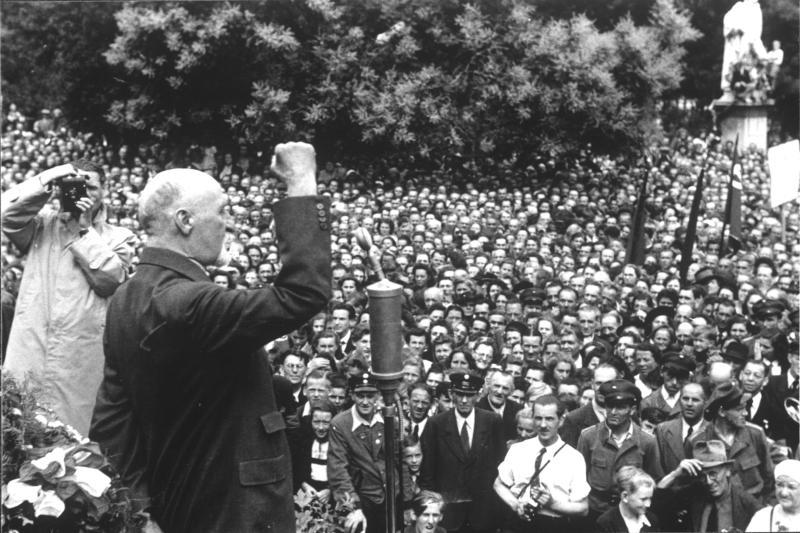 Seitz-Begrüßung, September 1945: Seitz vor Mikrophon spricht mit erhobener rechter Faust zu großer Menschenmenge am Rathausplatz
