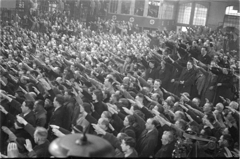 Großdeutscher Tag, April 1938; Halle mit NS-Fahnen, Menge bei Hitlergruß, Mann an Rednerpult