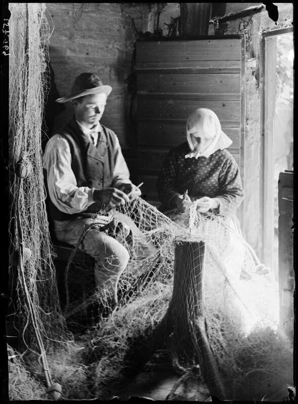 Fischerpaar beim Netze flicken.