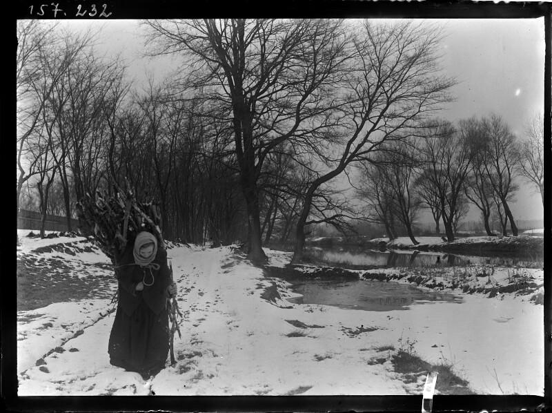 Frau mit Reisigbündel am Rücken