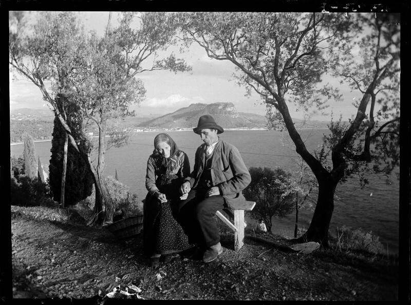 Altes Paar auf Bank über dem Gardasee