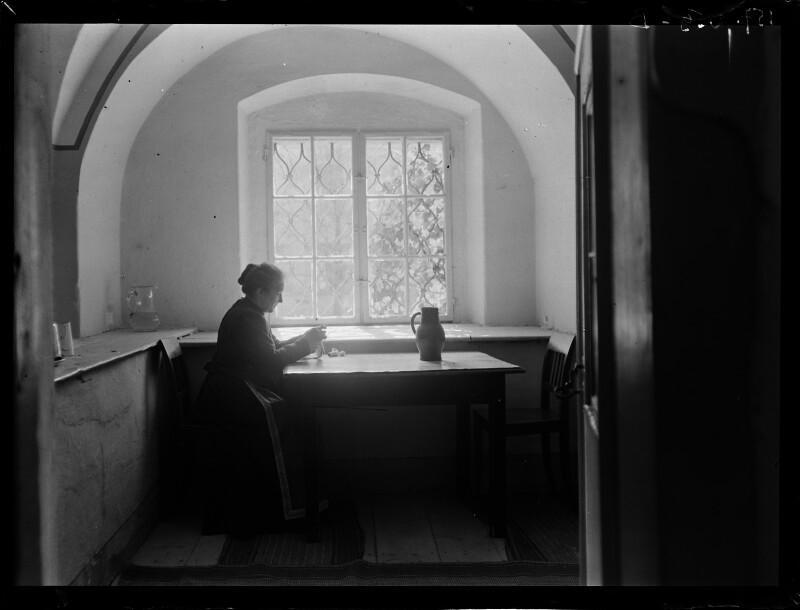 Alte Frau strickend beim Fenster