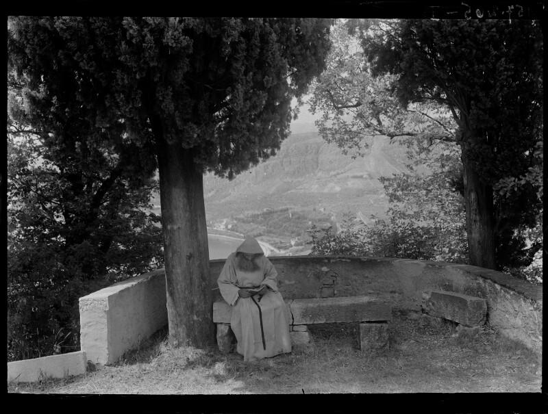 Lesender Mönch auf einer Steinbank