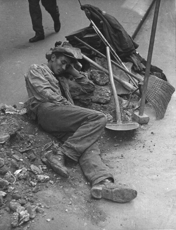 Ein Straßenarbeiter hält am Rinnstein kurze Rast