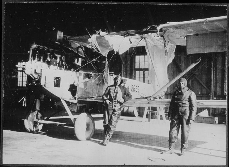 Piloten vor einem beschädigten Flugzeug