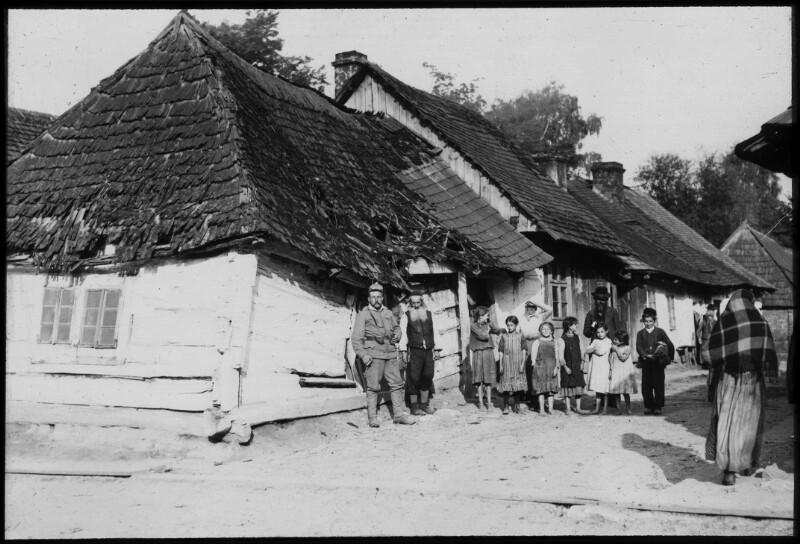Jüdische Familie posiert mit einem k.u.k. Soldaten vor einem fast zusammengefallenen Haus, möglicherweise Kisanow