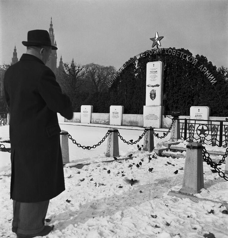 Mann füttert Vögel am Grab eines Soviet Soldaten, im Hintergrund ist das Wiener Rathaus zu sehen