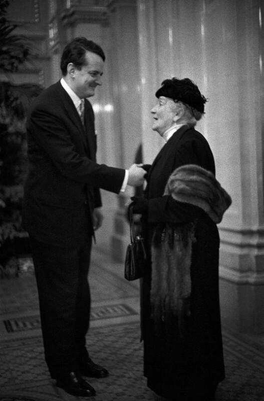 """Gottfried von Einem begrüßt die Witwe des Komponisten Wilhelm Kienzl in einer Pause während der Aufführung von Beethovens """"Fidelio"""" anlässlich der Wiedereröffnung der Wiener Staatsoper 1955."""