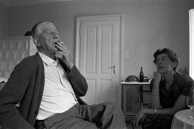 Maler Oskar Kokoschka genießt eine Zigarette bei sich zu Hause, seine Frau Olda ist im Hintergrund zu sehen, Villeneuve, Switzerland, 1959
