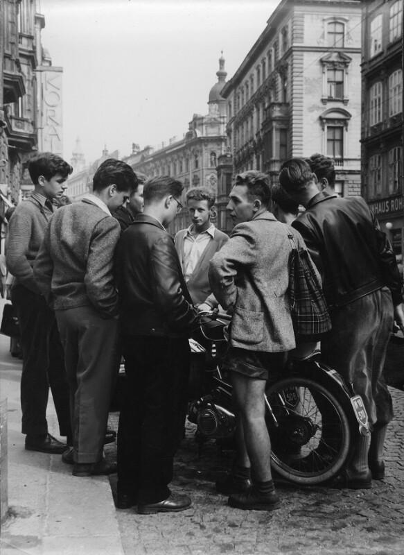 Jugendliche stehen um ein Moped
