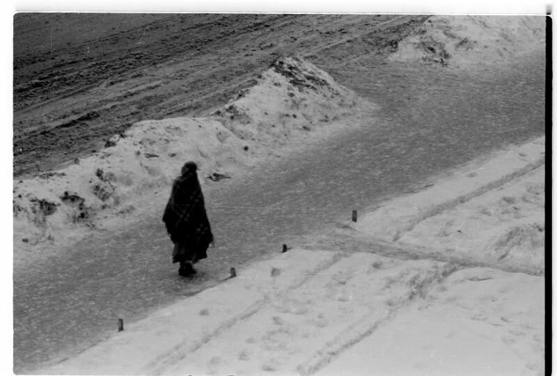 Einsame Gestalt auf schneebedeckter Straße