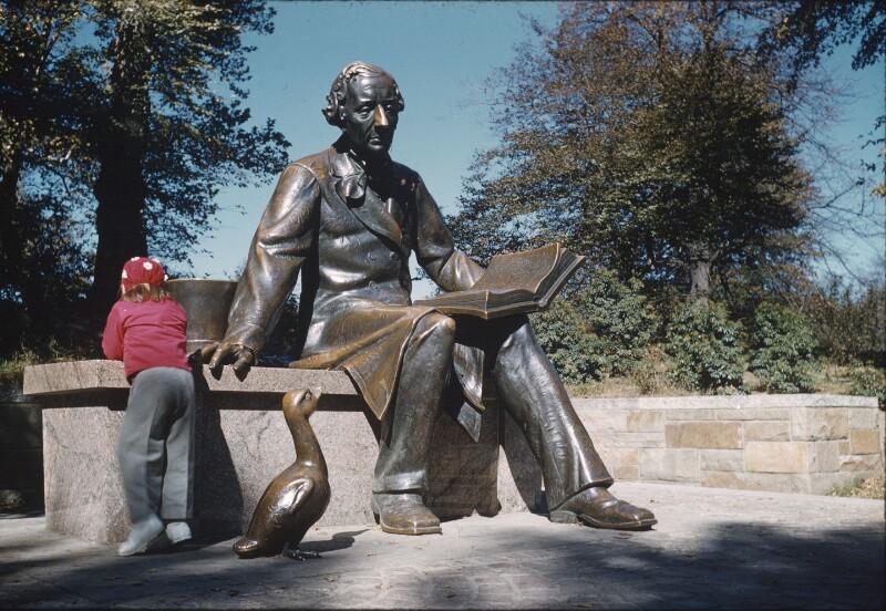 Kind von hinten neben Statue von Hans Christian Andersen