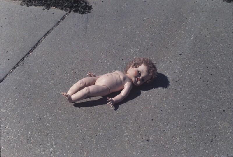 Nackte Puppe am Asphalt