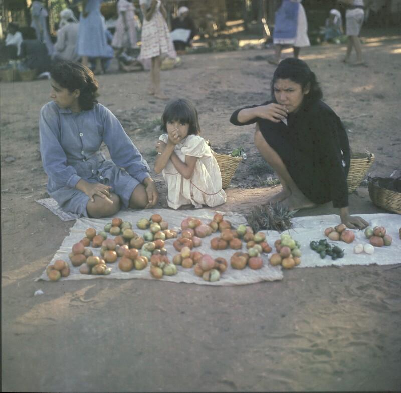 Frauen und ein Mädchen beim Verkauf von Obst