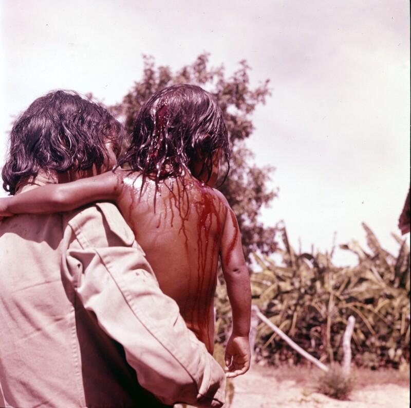 Mensch mit nassem Kind am Arm, Brasilien