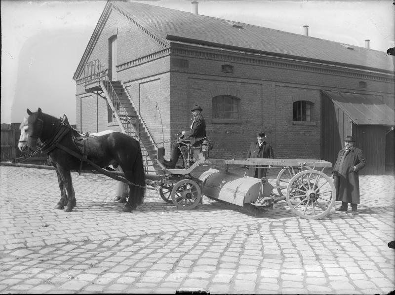Straßenkehrmaschine mit Pferden bespannt