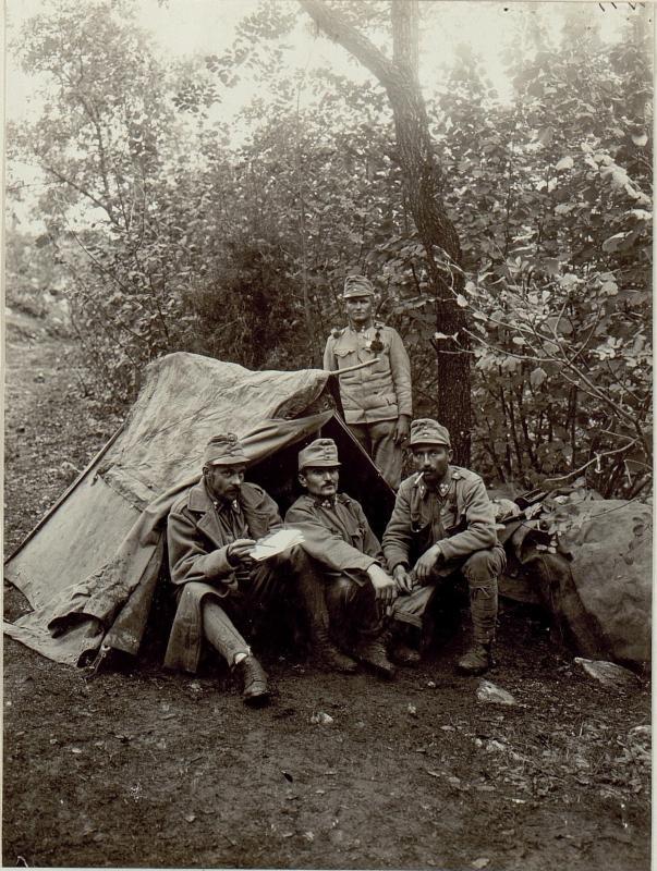 Unteroffizier, vorne rechtshockend mit der kleinen silbernen Taferkeitsmedaille, hinten stehend mit der großen silbernen Tapferkeitsmedaille dekoriert, beim Zelt