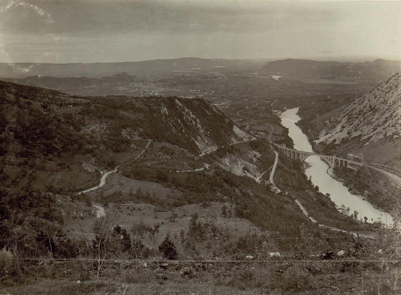 Totalansicht von Görz mit der Eisenbahnbrücke von Salcano im Vordergrund, im Hintergund das Doberdo-Plateau