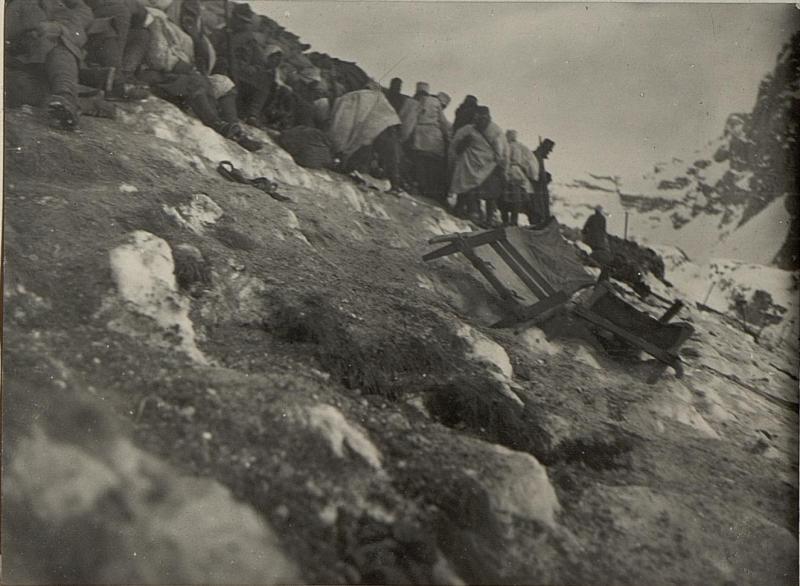 Am Cuklagipfel. Die Mannschaft sucht gegen das Artillerie-Feuer Deckung hinter der italienischen Sandsackmauer.