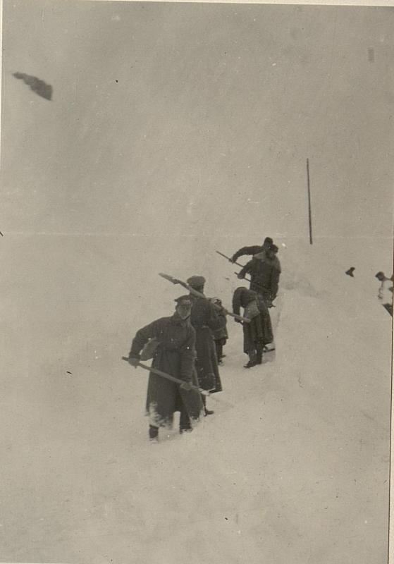 Schnee schaufelnde Russen auf dem Oregonesattel im Schneetreiben.