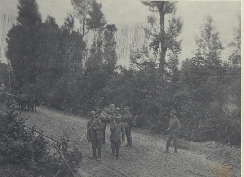 Von gefangenem Italiener getragener Verwundeter bittet um Feuer.