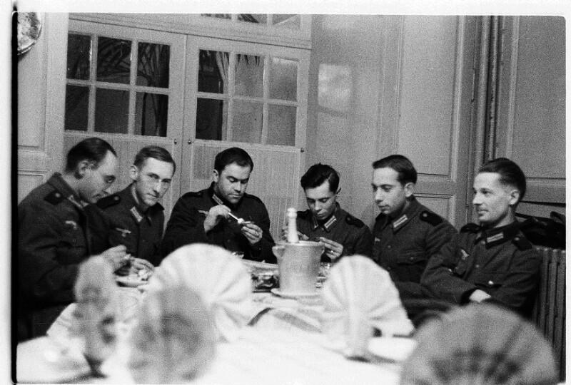 Joe J. Heydecker (letzter rechts) und seine Kameraden bei Tisch mit Champagner und Austern