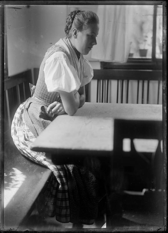 Frau in Tracht in einer Sitzecke von Schmutzer, Ferdinand