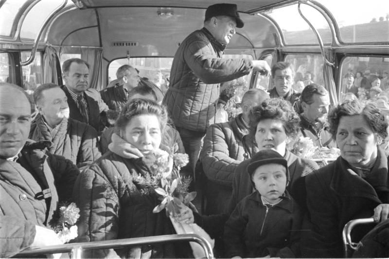 Heimkehrer - Bad Vöslau - sitzen im Autobus, ein Heimkehrer steht, schaut in die Menschenmenge, die um den Bus versammelt ist von Kern, Fritz