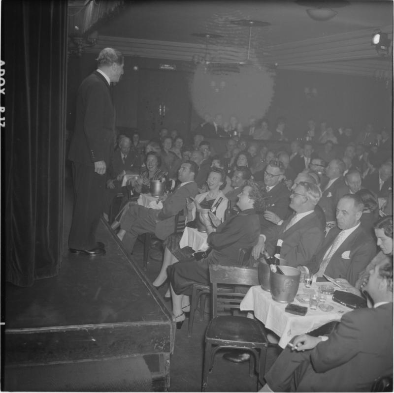 Karl Farkas auf der Bühne und Publikum. Kabarett Simpl von Scheidl