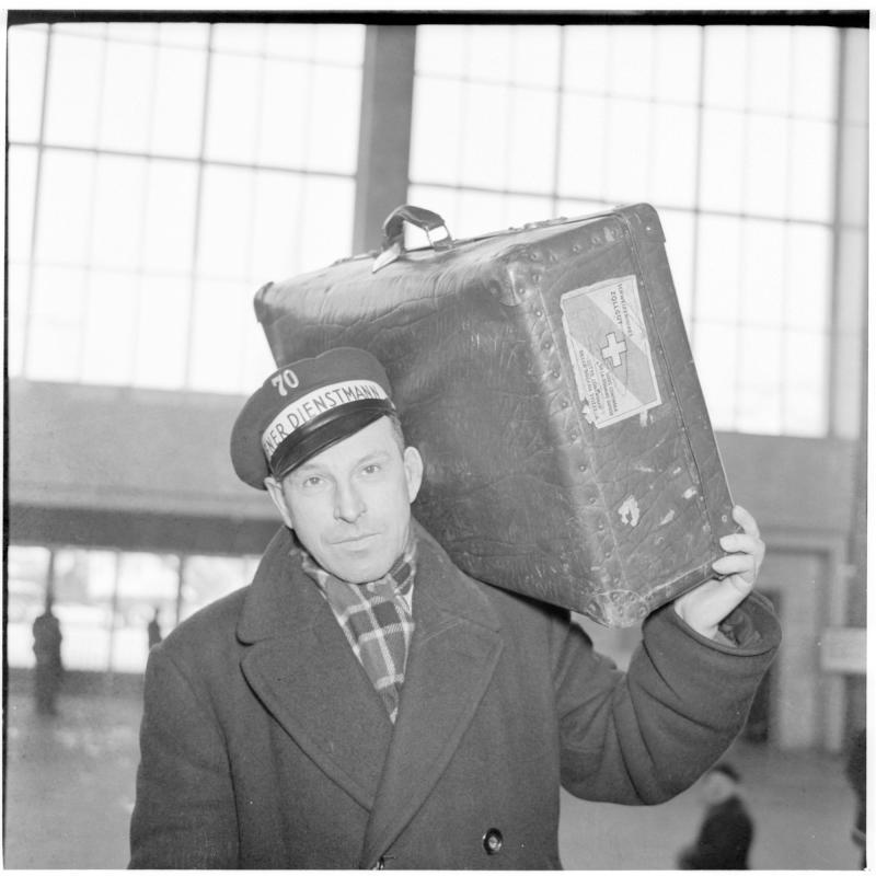 Dienstmann trägt Koffer auf der Schulter. Dienstmänner am Westbahnhof von Scheidl