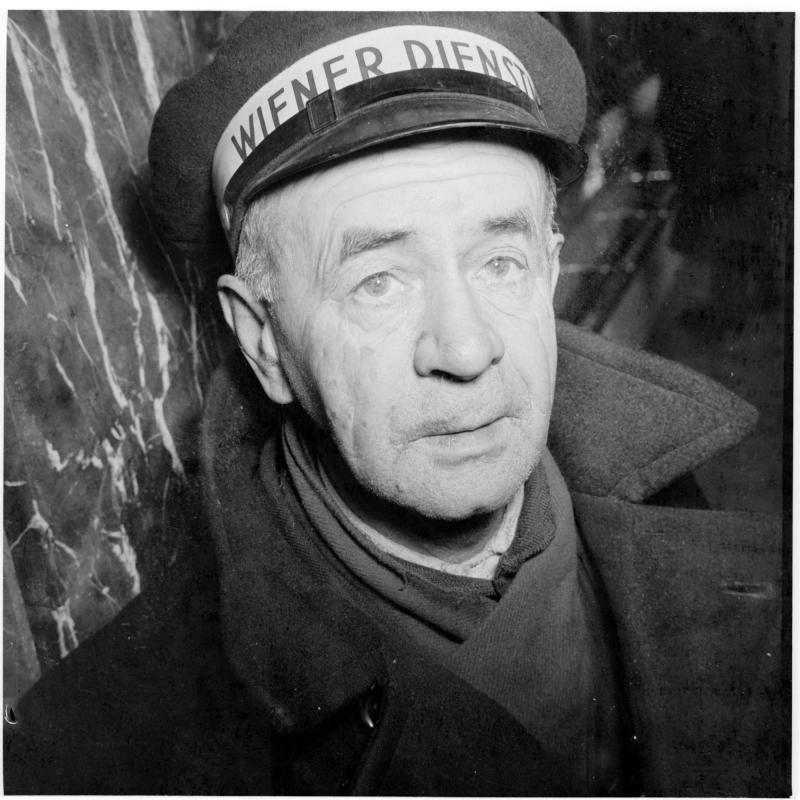 Porträt eines älteren Dienstmannes in der Bahnhofshalle. Dienstmänner am Westbahnhof von Scheidl