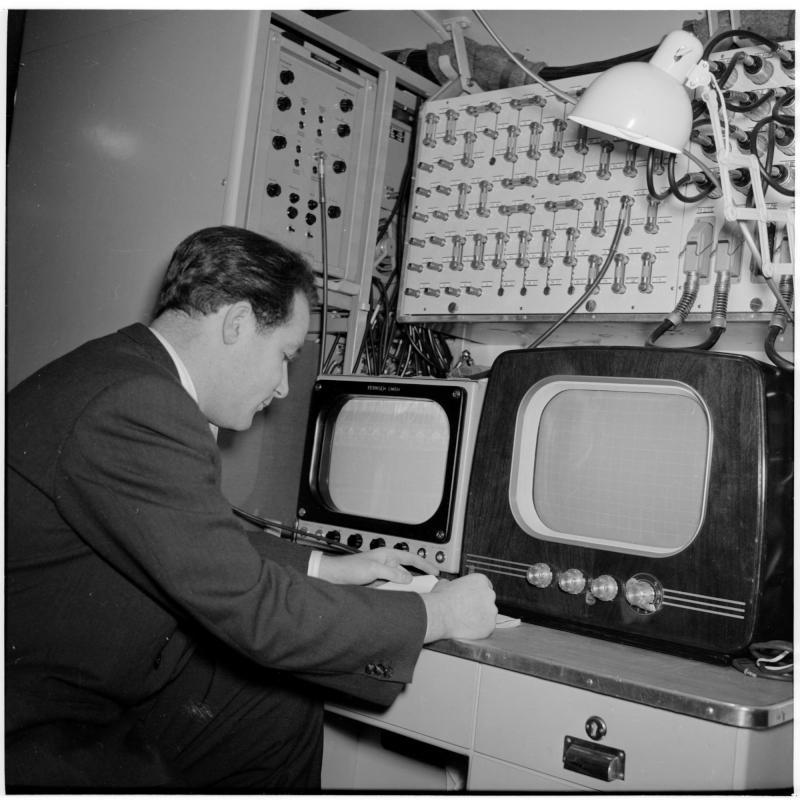 Mann in einem Ü-Wagen sitzt vor zwei Fernsehern. Fernsehwagen von Scheidl