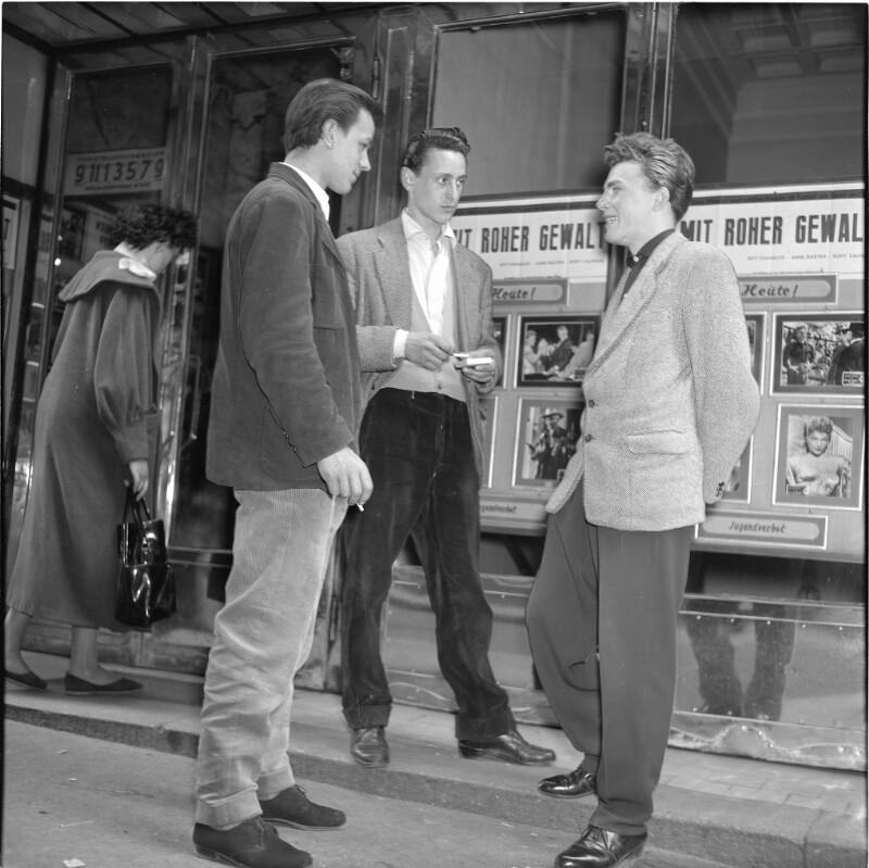 Drei Burschen stehen vor einem Kino, unterhalten sich, im Hintergrund Schaufenster mit dem Kino-Programm, zwei der Burschen rauchen. Halbstarke vor Kino von Scheidl