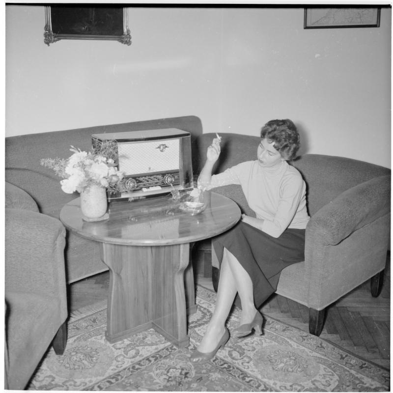 Frau sitzt bei neuem Philips-Radio, raucht eine Zigarette. Frau mit neuem Philips-Radio von Scheidl