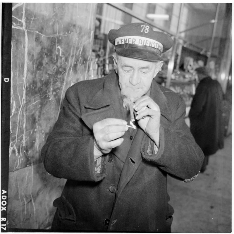 Dienstmann in der Halle des Westbahnhofs, zündet sich eine Zigarre an. Dienstmänner am Westbahnhof von Scheidl