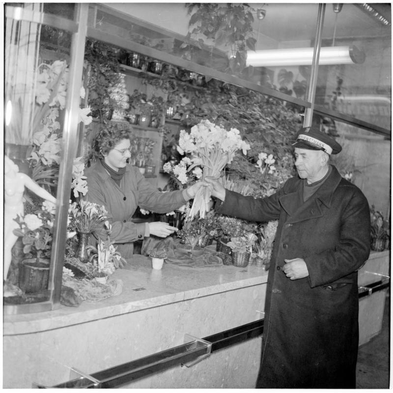 Dienstmann in der Halle des Westbahnhofs, kauft einen Blumen-Strauß beim Blumen-Stand. Dienstmänner am Westbahnhof von Scheidl