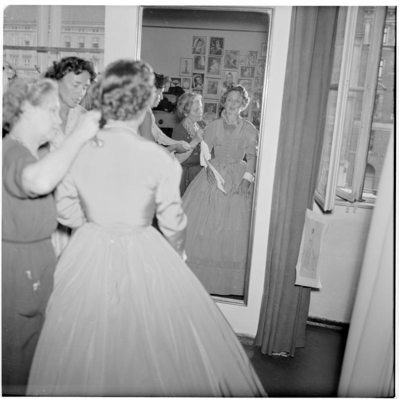 Frau probiert ein historisches Kleid, sie betrachtet sich im Spiegel. Romy Schneider und Karlheinz Böhm von Scheidl