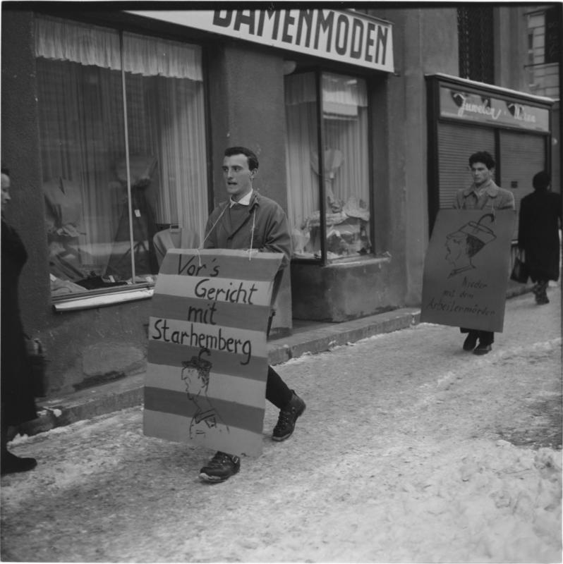 Demonstranten mit Transparent-tafeln gegen den ehemaligen Minister Starhemberg - u.a. 'Vor's Gericht mit Starhemberg', 'Nieder mit dem Arbeitermörder' von Scheidl