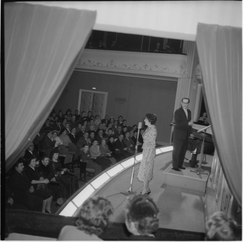 Blick von Loge auf Bühne und Publikum; Frau vor Mikrophon, neben ihr Dirigent. Letzte Rundfunkübertragung aus dem Burgtheater von Scheidl