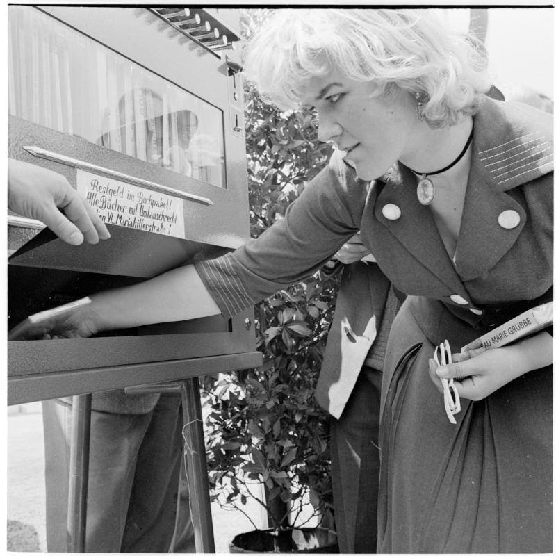 Frau nimmt ein Buch aus dem Automaten. Buch-Automat der Firma Herzog von Scheidl