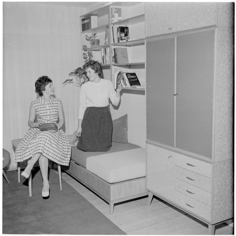Junge Frau sitzt auf einem Sessel mit einem Täschchen in der Hand, daneben kniet eine junge Frau am Bett, sie unterhalten sich. Wie Teenager wohnen von Scheidl