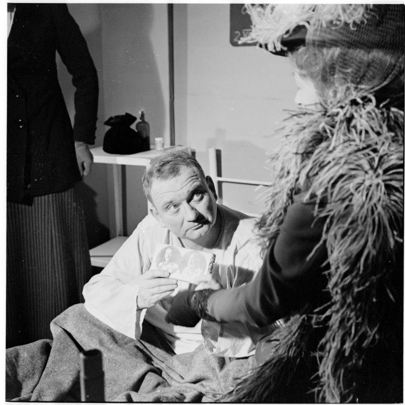 Szene mit Fritz Muliar und Marianne Schönauer, Muliar liegt im Krankenbett, zeigt ein Foto. 'Schweijk' von Scheidl
