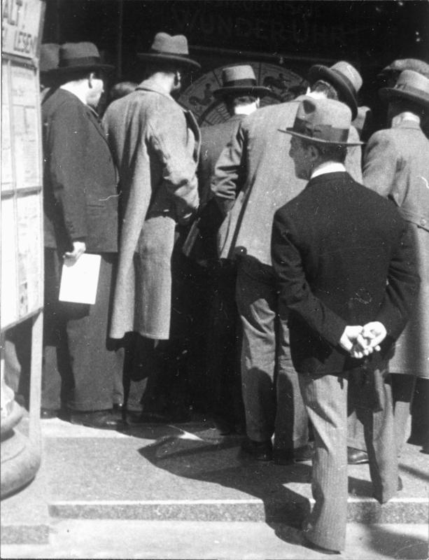 Menschen umringen den Astrologen, ein Mann betrachtet ein Plakat mit der Überschrift 'HALT! WICHTIG! LESEN!', auf der anderen Seite ein PLakat mit der Aufschrift 'WUNDER-UHR'