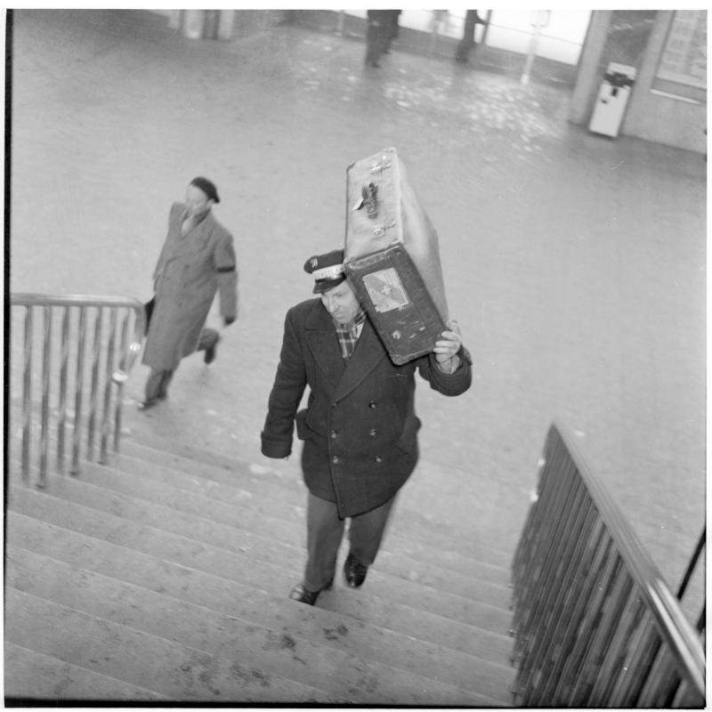 Dienstmann mit Koffer auf der Schulter geht Stiegen rauf. Dienstmänner am Westbahnhof von Scheidl