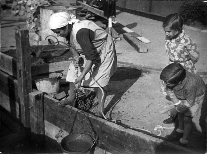 Bauarbeiten, eine Frau zieht einen Eimer hoch, zwei kleine Kinder sehen ihr neugierig dabei zu - ein Mädchen und ein Bub
