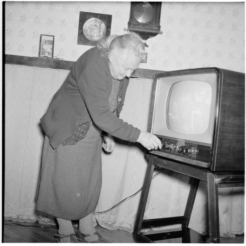 Alte Frau beim Einschalten eines Fernsehers. von Scheidl